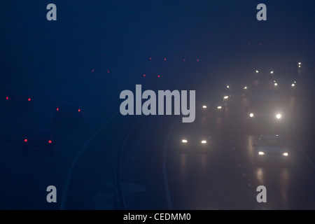 Voitures dans le brouillard sur la route en Angleterre dans la nuit