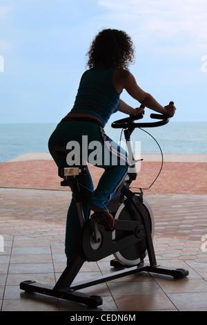 Silhouette de fille sur l'appareil de formation au cyclisme outdoor le beach Banque D'Images