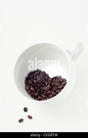 Trois haricots renverser de groupe en forme de cœur de grains de café niché dans de grandes tasses à café blanc. Banque D'Images