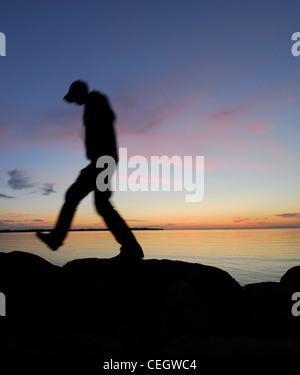 Silhouette of man walking par un lac dans la nuit Banque D'Images