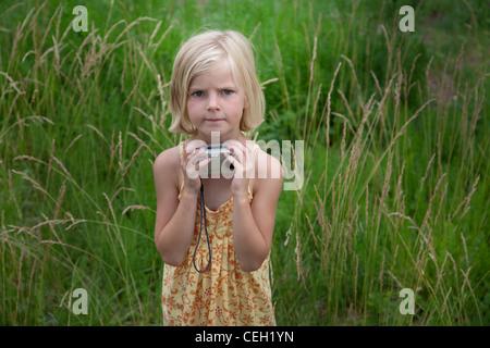 Portrait d'une jeune fille tenant un appareil photo numérique dans un champ d'herbe Banque D'Images