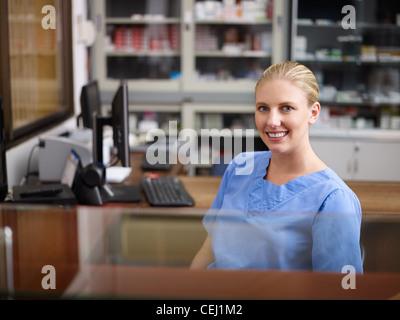 Jeune femme au travail comme réceptionniste et l'infirmière à l'hôpital, looking at camera Banque D'Images