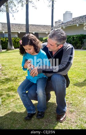 Un enfant de cinq ans Egyptian-American fille est réconforté par son père alors qu'elle grimace de douleur d'un mal d'estomac