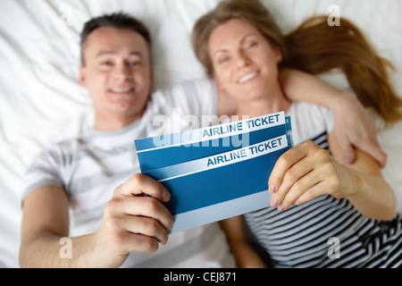 Happy young couple lying on bed with billets d'avion dans les mains Banque D'Images
