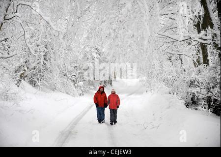 Un couple de manteaux d'hiver rouge correspondant à marcher en voie de Cotswold par temps neigeux UK Banque D'Images