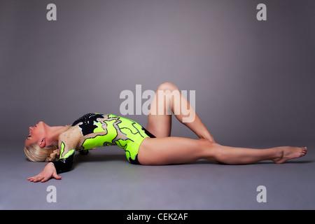 Jeune femme en costume gymnaste jeter sur fond gris, ambiance détendue Banque D'Images