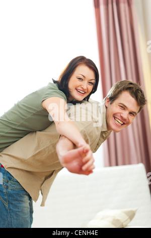 Smiling young couple in love s'amuser à la maison Banque D'Images