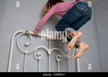 Girl jumping on bed Banque D'Images