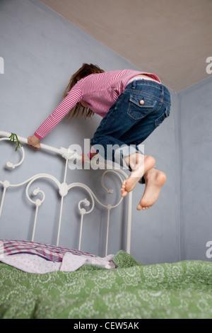Sept ans girl holding cadre de lit et de sauter haut au-dessus de son lit. Banque D'Images