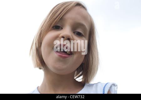 Six ans smiling avec grand écart, l'absence de dents de devant, le ciel en arrière-plan. Banque D'Images