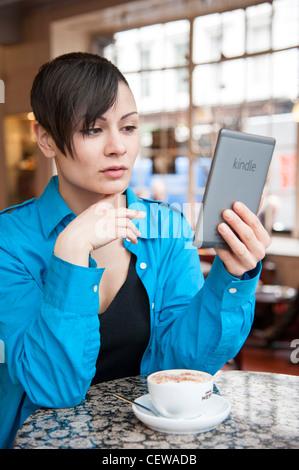 Jeune femme lisant un livre électronique sur Amazon Kindle, UK Banque D'Images