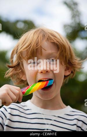 Boy eating lollipop Banque D'Images