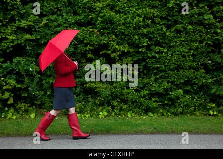 Photo d'une femme en rouge marchant le long d'une route avec son parapluie en place
