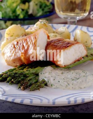 Plaque bleu et blanc filet de poisson blanc grillé enveloppé dans du jambon de Parme coupé en deux, asperges grillées, Banque D'Images