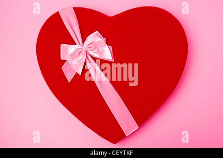 Saint Valentin en forme de coeur rouge boîte de chocolats à égalité avec ruban rose, dans la région de bow Banque D'Images