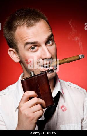 Jeune homme confiant avec flasque et de cigare Banque D'Images