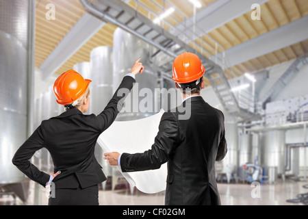 Architects holding blueprints et à la recherche dans un site de construction Banque D'Images