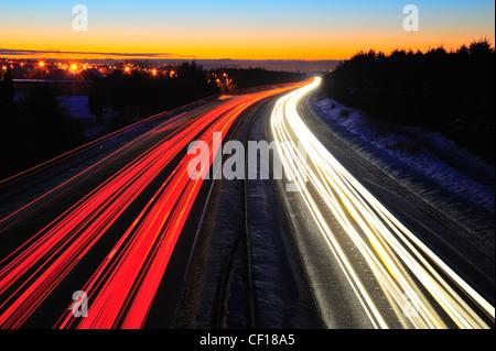 Sentiers de feux de circulation sur l'autoroute M8 en Ecosse entre Glasgow et Édimbourg. Prises de nuit dans l'hiver Banque D'Images