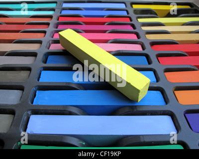 Nouveaux pastels chalk inutilisés dans une boîte avec un jaune située au-dessus. Banque D'Images