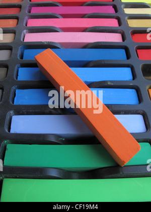 Nouveaux pastels chalk inutilisés dans une boîte avec un rouge située au-dessus. Banque D'Images