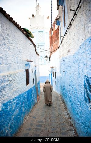 Muslim man walking in the blue remparts de la vieille médina de Chefchaouen, Maroc