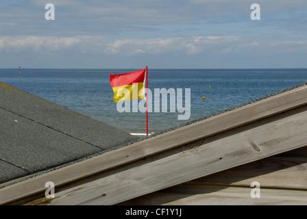 Un drapeau de baignade vu entre les toits de deux cabines de plage. Le drapeau de baignade marque une fin d'une Banque D'Images