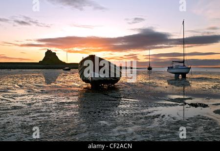 Le lever du soleil sur des bateaux amarrés à marée basse avec une vue sur le château à Lindisfarne. Banque D'Images