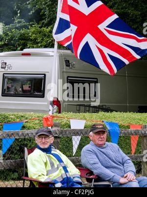 Deux hommes assis sous un drapeau de l'Union à l'Audley End Gala 2011 de la vapeur. Banque D'Images