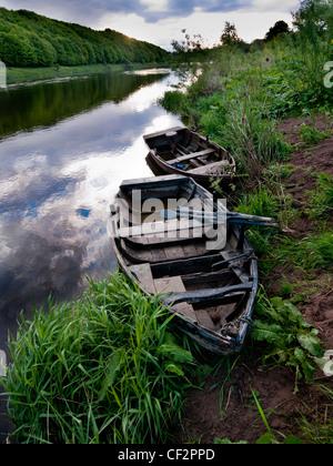 Vieux bateaux de pêche sur les rives de la rivière Tweed. Banque D'Images