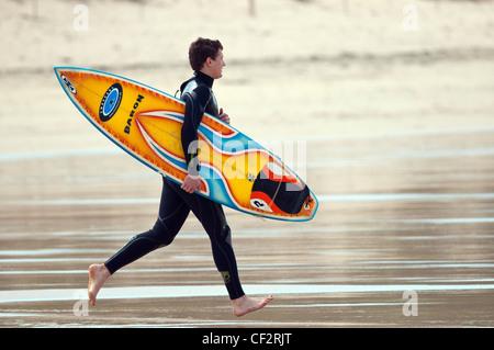 Un surfeur en travers de la plage de Fistral, son surf.