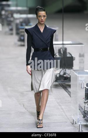 Modèle Mariacarla Boscono italien portant veste noire sans manches  ceinturée envelopper les épaules en avant, 79d29f28d63