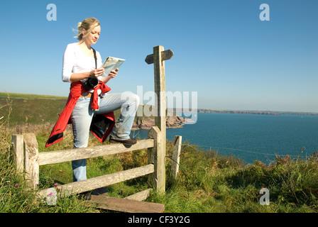 Une femelle Walker s'arrête sur un stile de lire une carte sur la falaise au-dessus de la tête à Ann au Pays de Banque D'Images