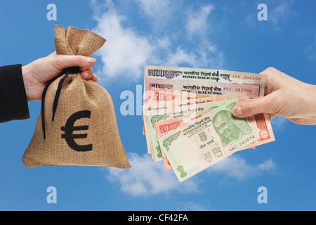 Nombreux sont les projets de roupie indienne tenue à la main. De l'autre côté un sac avec de l'argent est signe Banque D'Images