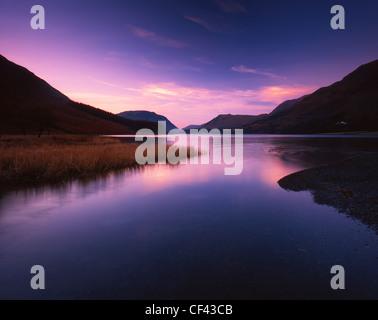 La recherche à travers les eaux calmes de la lande dans le district du lac au coucher du soleil. Banque D'Images