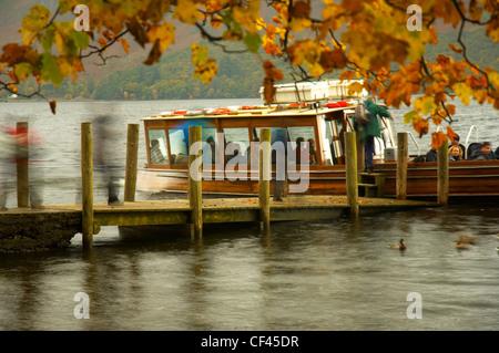 Les touristes pour monter et descendre d'un bateau de croisière Derwentwater en automne. Banque D'Images