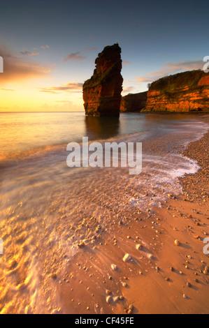 Lever du soleil à l'aube Ladram Bay sur la côte jurassique du Devon. Banque D'Images