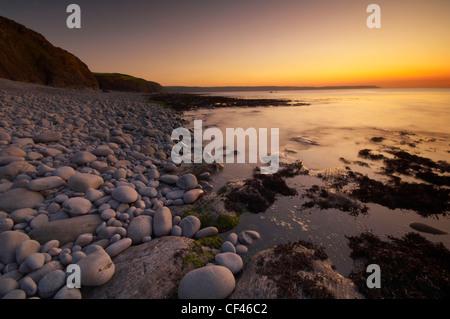 Coucher de soleil sur la plage de rochers à Abbotsham sur la côte nord du Devon. Banque D'Images