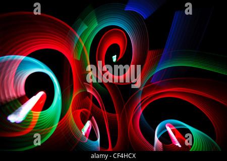 Résumé des motifs lumineux en forme de spirales sur fond noir. Banque D'Images
