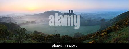 Vue vers l'ouest de Corfe Castle Hill sur un lever de soleil brumeux. Banque D'Images