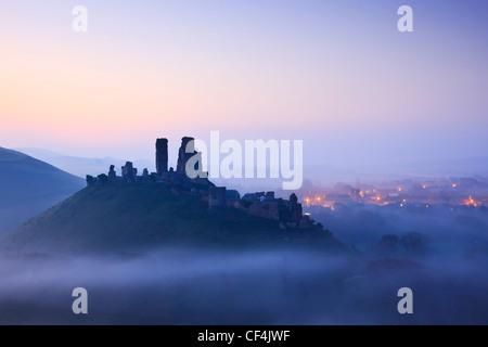 Château de Corfe, remontant au 11e siècle, avant l'aube se lever au-dessus de la brume. Banque D'Images