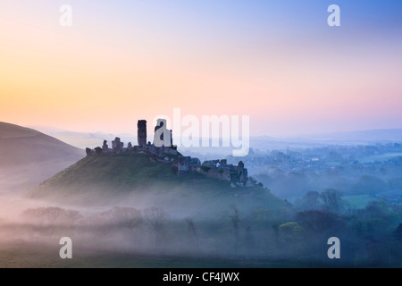 Château de Corfe, remontant au 11e siècle, dans la brume au lever du soleil. Banque D'Images