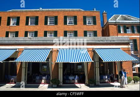 Un couple debout sur une terrasse à l'extérieur d'un restaurant à Woodcote Park, un club privé dans les North Downs Banque D'Images