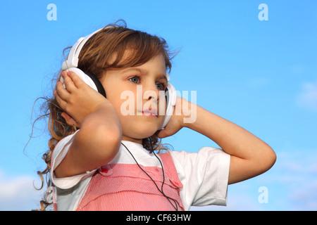 La jolie petite fille, contre le bleu du ciel, écoute de la musique à travers les écouteurs. Banque D'Images
