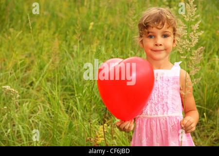 Belle petite fille en robe rose tenue ballon rouge. Fille sur la nature Banque D'Images