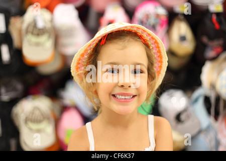 Portrait de petite fille en essayant le panama en magasin et souriant, avec les produits de comptoir Banque D'Images