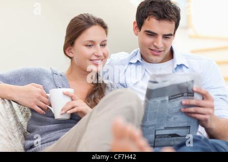 La lecture de l'actualité couple en position allongée sur un canapé Banque D'Images