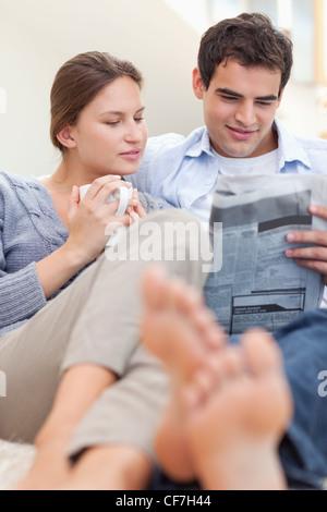 Couple lire un journal tout en étant allongé sur un canapé Banque D'Images