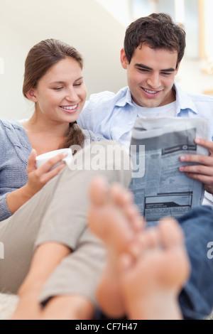 Couple lire un journal tout en étant allongé sur un divan Banque D'Images