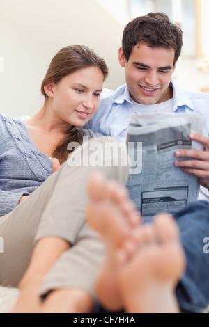 Portrait d'un couple lire un journal tout en étant allongé sur un divan Banque D'Images