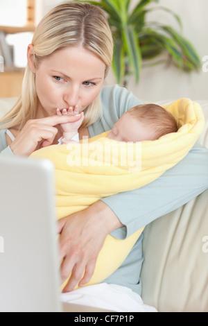 Mère embrassant la main de son bébé tout en regardant l'ordinateur portable Banque D'Images